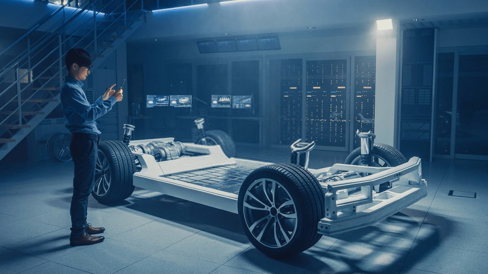 Automobile Engineer Working on Electric Car Chassis Platform, Using Tablet Computer Augmented Reality with 3D CAD Software Modelling