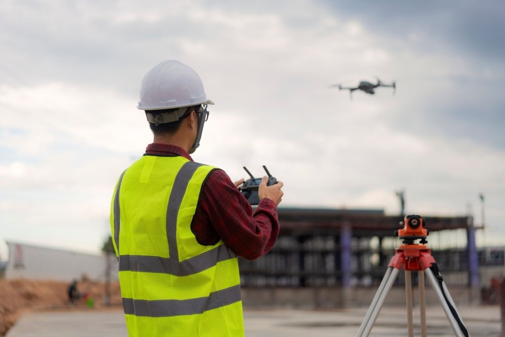 Asian construction worker piloting drone at building site.