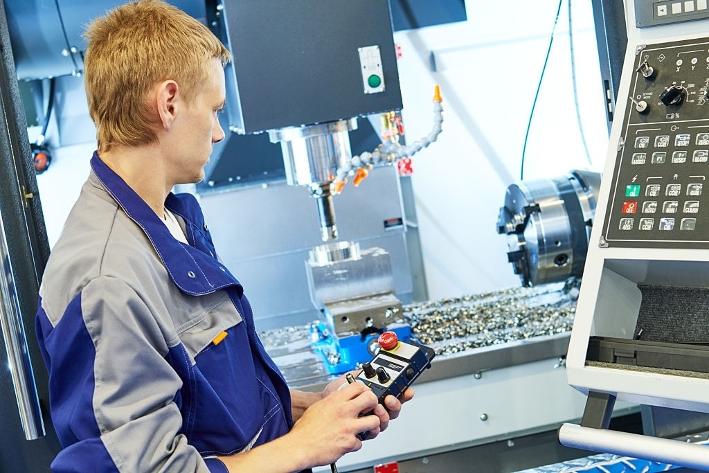 Service engineer operating CNC milling machine at factory. Image Courtesy of iStockPhoto